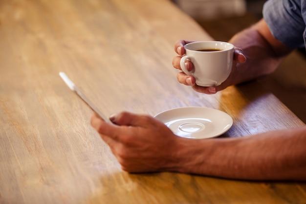 Обрезанное изображение битник человек с помощью смартфона, попивая чашку кофе Premium Фотографии