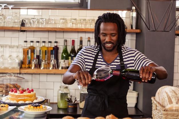笑顔のヒップスター従業員がワインのグラスを充填 Premium写真