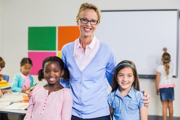 Портрет улыбающегося учителя и дети, стоя вместе с руки вокруг Premium Фотографии