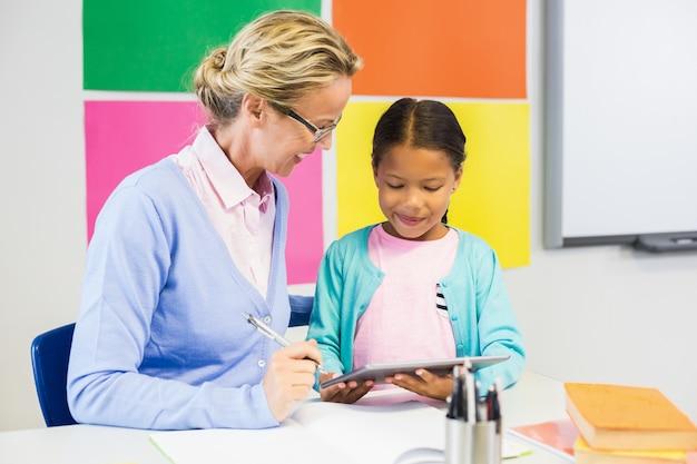女子高生と教師が教室でデジタルタブレットを使用して Premium写真