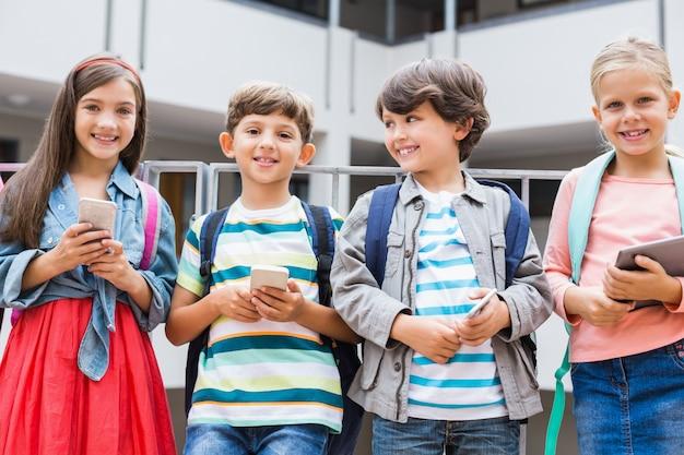 学校のテラスに立っている携帯電話とデジタルタブレットを保持している子供 Premium写真