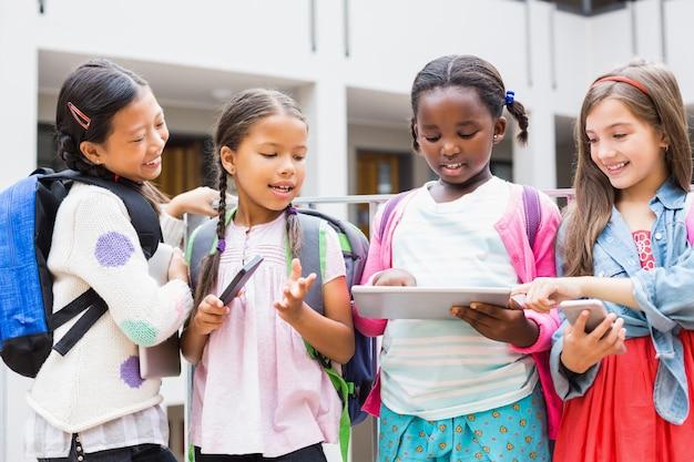 学校のテラスでデジタルタブレットと携帯電話を使用して子供たち Premium写真