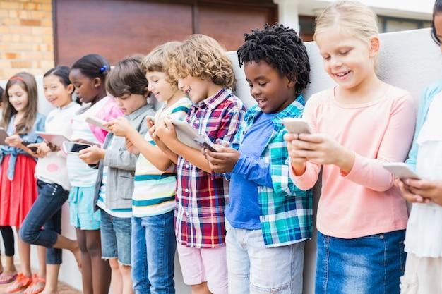 学校のテラスで携帯電話とデジタルタブレットを使用して子供たち Premium写真