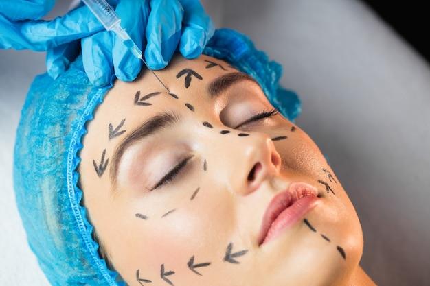 Женщина получает инъекцию на лоб Premium Фотографии