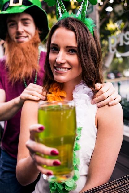 緑のパイントを保持している変装した女性 Premium写真