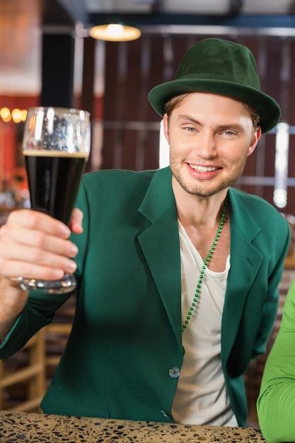 ビールを乾杯する帽子の男 Premium写真