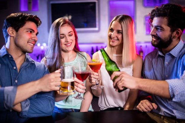 Группа друзей тостов коктейль, бутылка пива и бокал пива на барной стойке Premium Фотографии