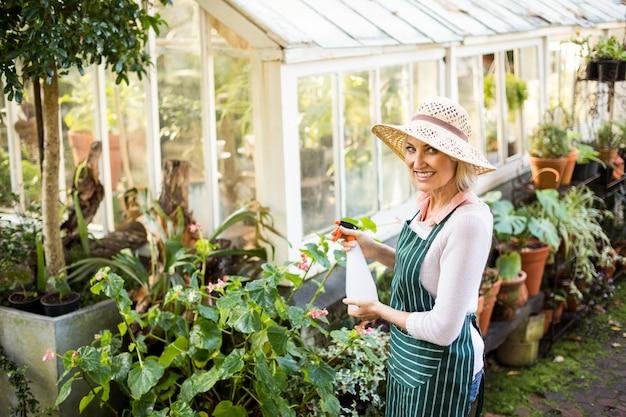 Счастливая женщина садовник поливает растения Premium Фотографии