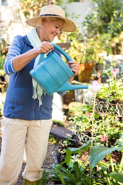 Счастливый садовник, распыления воды на растения в саду Premium Фотографии