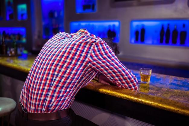 バーのカウンターの上に横たわる男の後姿 Premium写真
