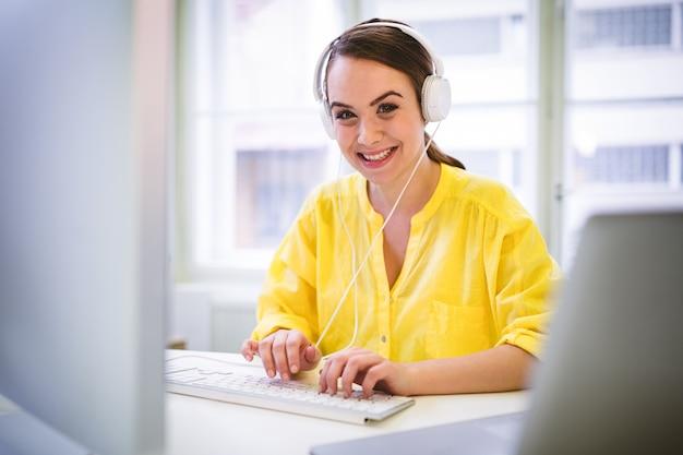 Портрет счастливой исполнительной власти пока печатающ на клавиатуре на офисе Premium Фотографии