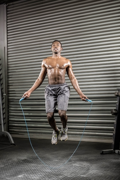 上半身裸の男がジムでロープをジャンプ Premium写真
