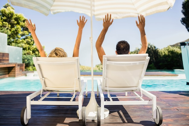 手を上げるとプールサイドのデッキチェアに横になっているカップルの背面図 Premium写真