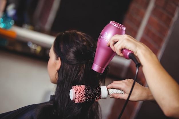 Женщина сушит волосы Premium Фотографии