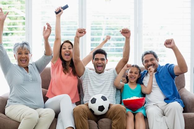 Счастливая многопоколенная семья смотрит футбольный матч по телевизору в гостиной Premium Фотографии