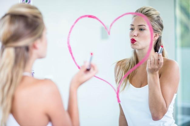 女性がトイレで口紅を適用します。 Premium写真