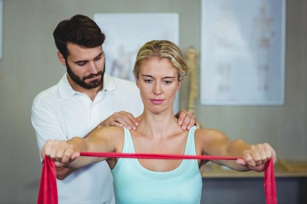 Мужской физиотерапевт дает массаж плеч пациентке Premium Фотографии