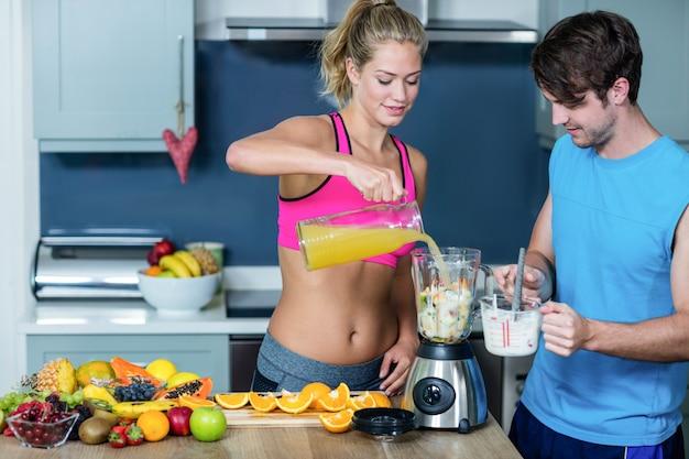 健康的なカップルが台所でスムージーを準備します。 Premium写真