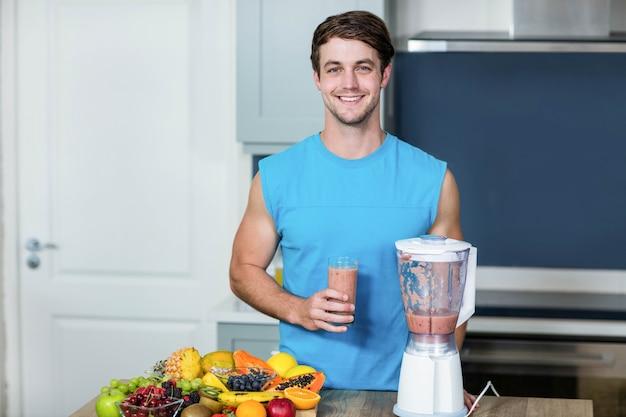 健康な人が台所でスムージーを準備します。 Premium写真