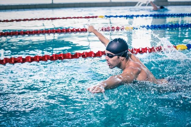 Красивый мужчина плавает в бассейне Premium Фотографии