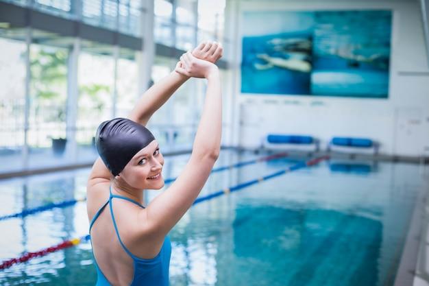 プールで彼女の腕を伸ばしてフィットの女性 Premium写真