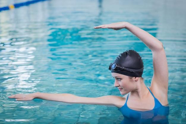 プールで水にストレッチフィットの女性 Premium写真