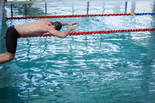 フィットのプールで水に飛び込む男 Premium写真