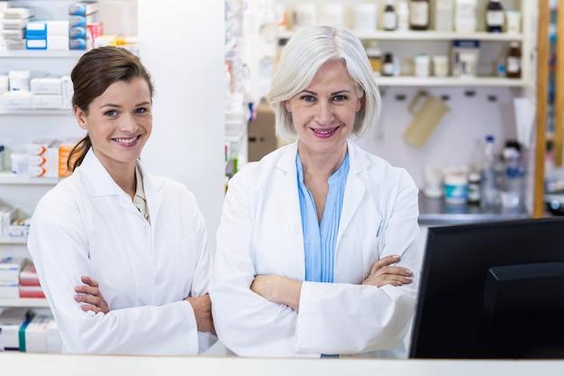 薬局で腕を組んで立っている笑顔の薬剤師 Premium写真