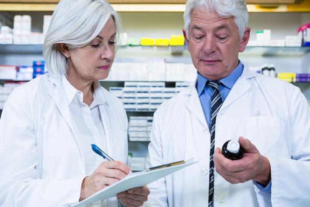 薬剤師は薬の処方箋をチェックして書く Premium写真
