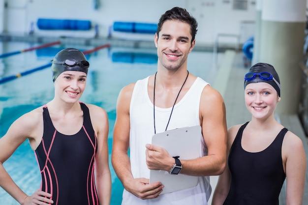 レジャーセンターでトレーナーと水泳選手の笑顔の肖像画 Premium写真