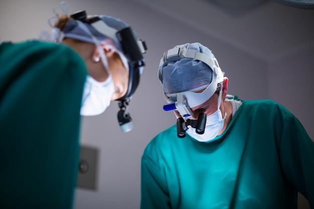 手術中に手術用ルーペを着用する外科医 無料写真