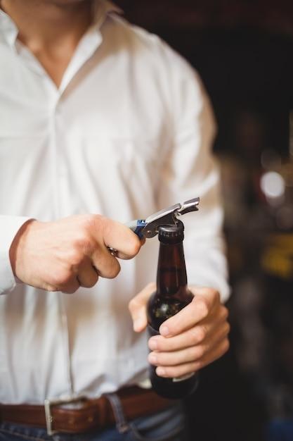 Средняя часть бармена открывает бутылку пива Бесплатные Фотографии