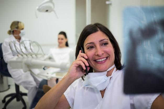 Стоматолог проверяет рентгеновский отчет во время разговора по мобильному телефону Бесплатные Фотографии