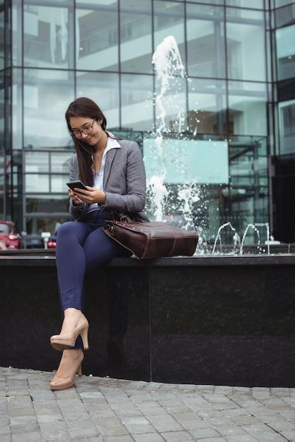 噴水の近くに座って、携帯電話を使用して実業家 無料写真