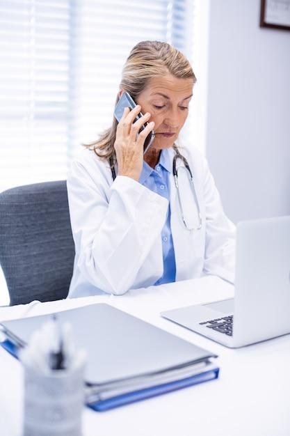 Женский доктор разговаривает по мобильному телефону Premium Фотографии