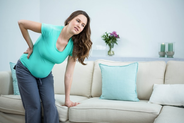 妊娠中の女性、リビングルームで背中の痛みを Premium写真
