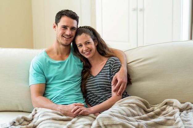 リビングルームのソファーで抱きしめる若いカップルの肖像画 Premium写真