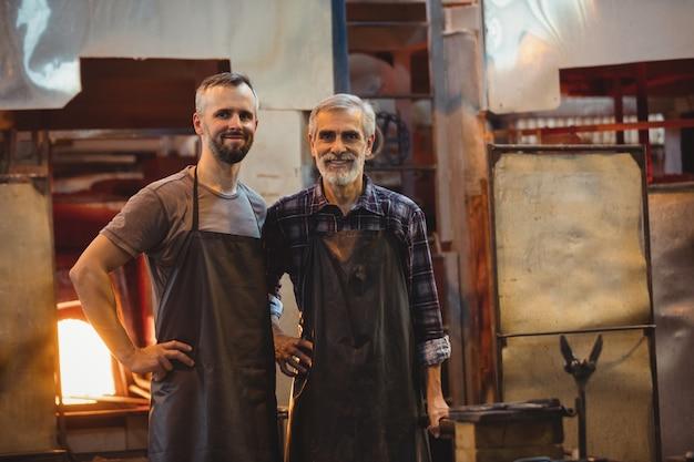 Портрет команды стеклодувов с руками на бедре Бесплатные Фотографии