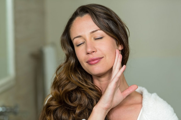 彼女の肌に触れると笑みを浮かべて美しい女性のクローズアップ Premium写真