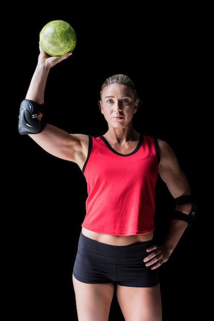 黒のハンドボールを保持している肘パッドを持つ女性アスリート Premium写真