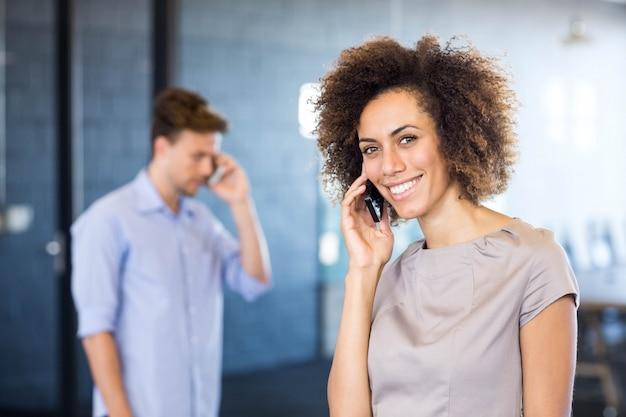 若い女性がオフィスの会議室の前に携帯電話で通信 Premium写真