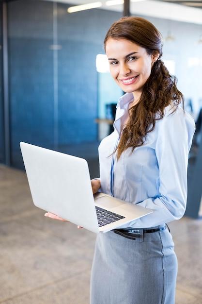 オフィスの会議室の前でラップトップを使用して若い女性の肖像画 Premium写真