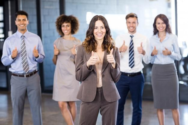 オフィスでの勝利を祝っている間彼らの親指を握って成功するビジネスチーム Premium写真