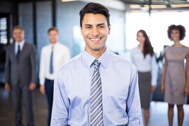 彼女の同僚がオフィスで彼の後ろに立っている間笑みを浮かべて成功するビジネス人 Premium写真