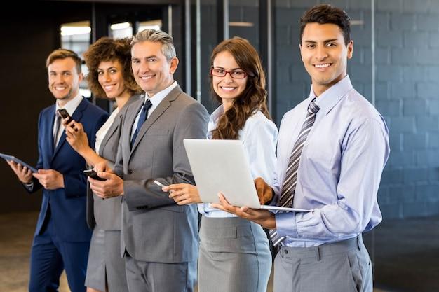 ビジネス人々が列に並んで、オフィスで携帯電話、ラップトップ、デジタルタブレットを使用して Premium写真