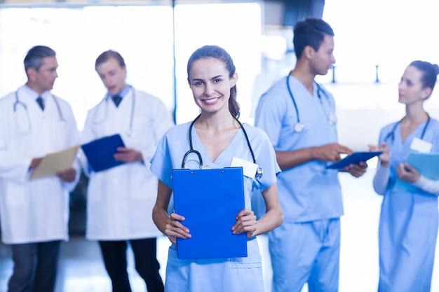 女性医師の医療レポートを保持していると彼女の同僚が議論しながら笑顔 Premium写真