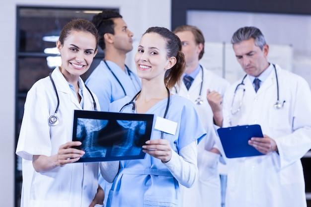 女性医師がレントゲン検査報告をチェックし、男性医師が後ろで議論している Premium写真
