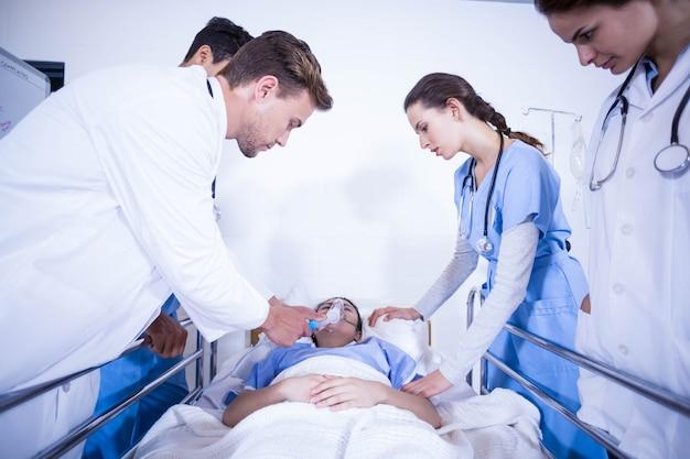 医師が病院でベッドの上で患者を調べる Premium写真