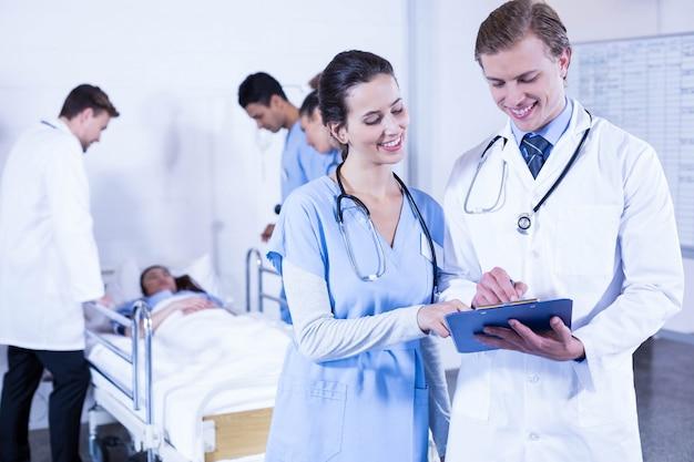 クリップボード上の書類と他の医者の後ろに患者を調べることを議論する医者 Premium写真