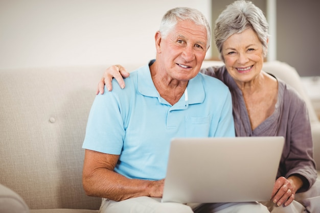 ソファに座っているとリビングルームで笑顔の年配のカップルの肖像画 Premium写真